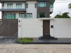 Lavish home walls feature small wooden doors for access and large sliding doors for cars.