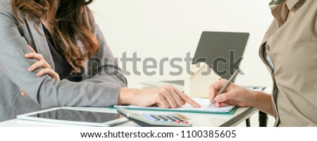 Law adviser is advising client. Customer signing document according to lawyer advise.
