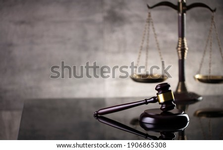 Law and justice concept. Mallet of the judge, hourglass, scales of justice. Gray stone background, reflections on the floor. Place for typography.