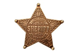 Law and justice in the wild west, American western culture and legal authority concept with picture of metal sheriff badge isolated on white background with clipping path cutout