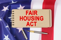 Law and order concept. Against the background of the flag of the United States of America lies a notebook with the inscription - FAIR HOUSING ACT