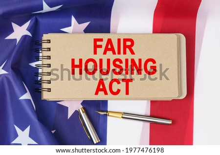 Law and order concept. Against the background of the flag of the United States of America lies a notebook with the inscription - FAIR HOUSING ACT Photo stock ©