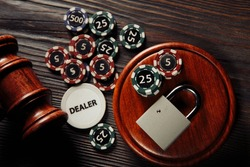 Law and rules for online gambling concept, judge gavel with padlock and aces on wooden background