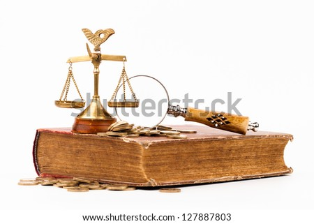 law book, magnifying glass and scales of justice