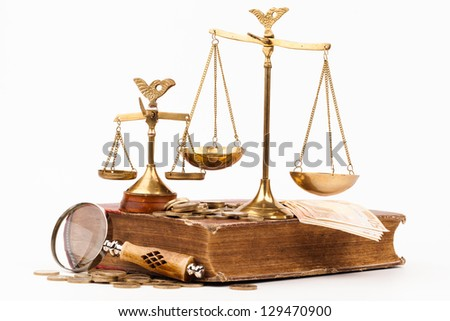 law book, magnifying glass and scales of justice isolated on white