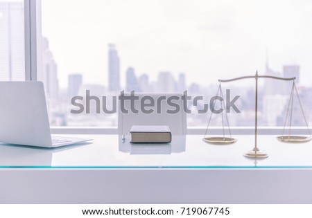law books,computer and scales of justice on desk in lawyer office and city view.