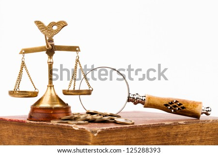 law books, money , magnifying glass and scales of justice
