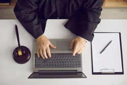 Law consultation and legal advice online: Professional senior judge, attorney or lawyer sitting at desk, working on laptop, doing web research or answering questions on website. High angle, from above