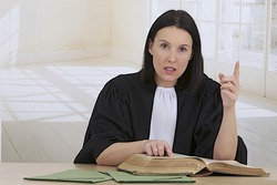 Law court concept. Young woman lawyer attorney wearing classic  french black white gown  preparing her speech for the defense with the big law book in her office