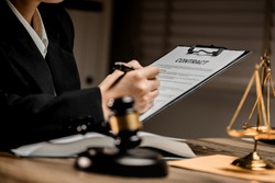 Law firm office, close up view of businesswoman or female lawyer reading the draft contract paper with law book, judges gavel, scales of justice, document legal, justice advice service concept.