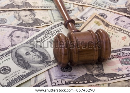 Law gavel laying on various denominations of American money.