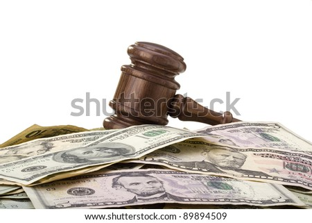 Law gavel laying on various denominations of American money. - stock photo