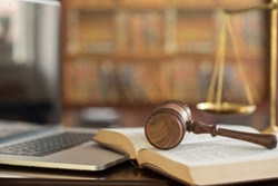 law legal technology concept.  judge gavel on book and computer with scales of justice on desk of lawyer.