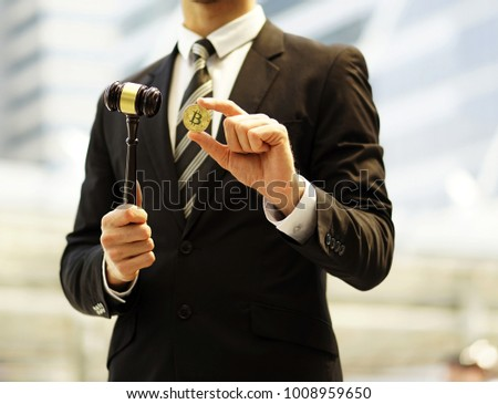 Law or auction gavel and bitcoin cryptocurrency golden coin. The young man holding hammer and bitcoin in hand. Wooden judge gavel with Golden Bitcoin coin (digital virtual money) holds bitcoin in hand