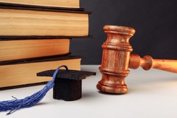 Law or education concept. Books with graduation cap and wooden gavel close-up