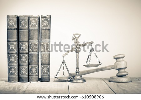 Law scales, wooden gavel and old books on table. Symbol of justice. Vintage style sepia photo