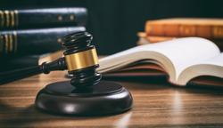 Law studies. Judge gavel on a wooden desk, blur legal books background