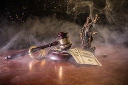 Law theme, mallet of the judge on wooden desk with Lady Justice Statue. Concept For Corruption, Justice, Law, Bankruptcy Court, Bail, Crime, Bribing, Fraud. Law gavel with handcuff and money