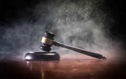 Law theme, mallet of the judge on wooden desk with Lady Justice Statue. Law gavel on dark foggy background with light. Selective focus