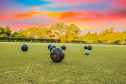 Lawn bowls balls in a field after the game with a colourful sunset