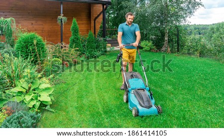 Lawn care. Mowing grass with an electric lawn mower. A young man mows the grass with a lawn mower with a grass collector on a sunny summer day. Beautiful landscape design in the garden.