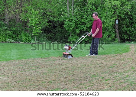 Lawn care showing a Man de-thatching his lawn