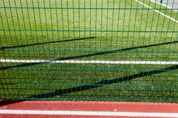 Lawn field for playing football behind the green fence mesh. Close-up of soccer field with green grass.