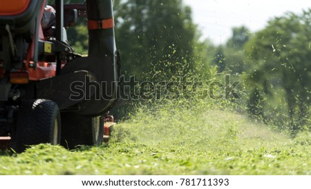 lawn mover at work on a green meadow at summertime #781711393
