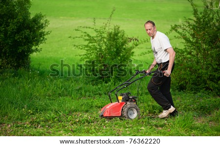Lawn mover. Gardener mowing green lawn.