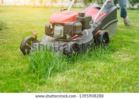 Lawn mower cutting green grass, gardener with lawnmower working, city courtyard of an apartment building #1395908288