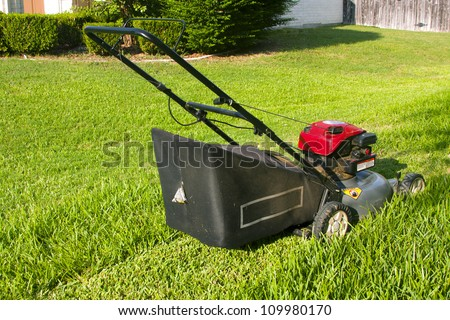 Lawn mower cutting pathway in grass