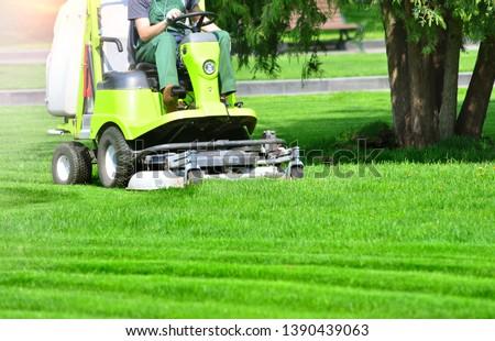 Lawn mower machine on a green lawn #1390439063