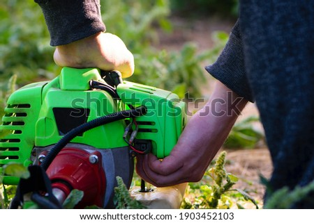 lawn mower motor, male hands. Man Checking the fuel level in the lawn mower. Green lawn mower. Gardening. Equipment service. Lawn mower maintenance. Service person. close-up Foto stock ©