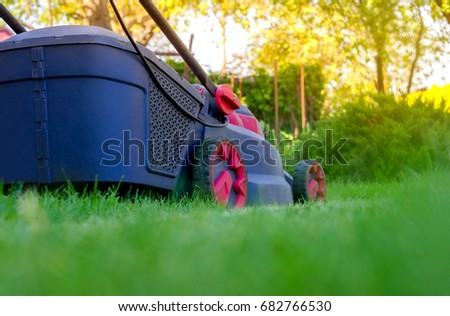 lawn mower mows a grass on a lawn, care of a lawn #682766530