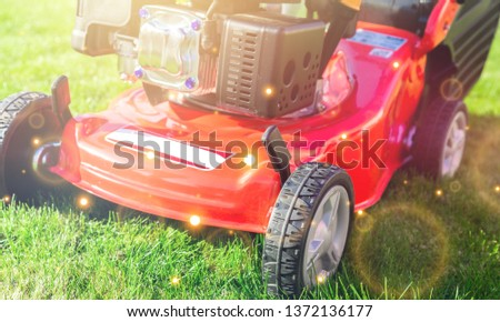 Lawn mower on a lawn in the garde #1372136177