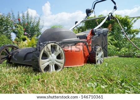 Lawn mower on a lawn in the garden / gardening