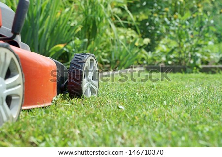 Lawn mower on a lawn in the garden / gardening