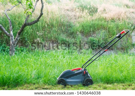 Lawn mower on a lawn. The lawn mower on the grass in the countryside yard #1430646038