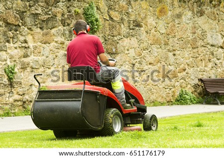 lawn mower on green lawn by professional gardener #651176179