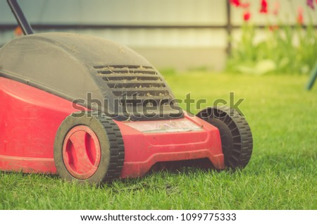 lawn mower on the lawn/red lawn mower on summer meadow. Selective focus #1099775333