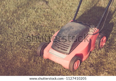 lawn mower on the lawn/red lawn mower on summer meadow. Toned and copyspace #1127410205