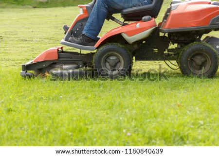 lawn mower tractor working in the town park #1180840639