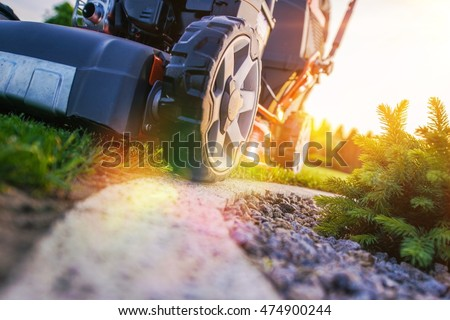 Lawn Mowing Closeup Photo. Professional Landscaping Works. Grass Cut. #474900244