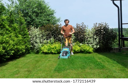 Lawn mowing in a beautiful landscape. An adult man using a lawn mower with a grass catcher mows overgrown grass on the lawn.