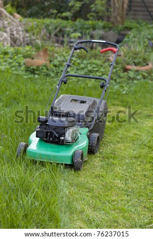 lawnmower. half cutted green lawn.