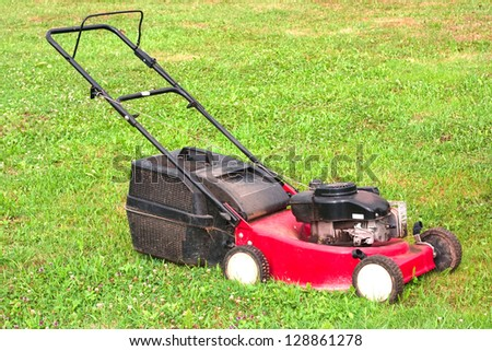 Lawnmower standing on green grass partly mowed but part still left to mow
