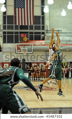 LAWRENCEVILLE, NJ - JANUARY 28: Rider University basketball player Justin Robinson (white) goes up for a three point shot late in the January 28, 2010 MAAC conference game in Lawrenceville, NJ.