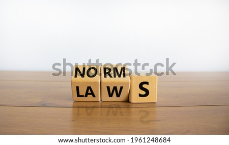 Laws or norms symbol. Turned cubes and changed the word 'norms' to 'laws'. Beautiful wooden table, white background, copy space. Business and laws or norms concept. Photo stock ©