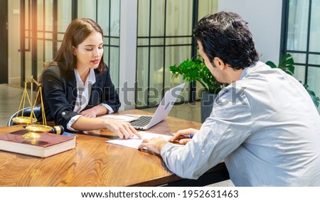 Lawyer gives legal advice and talks to her clients for advice on the rules and regulations that must be followed at the Office of Legal Counsel.  Foto stock ©
