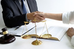 Lawyer or judge  with gavel and balance handshake with client or customer about agreement how to  use arbitration